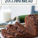 Sliced loaf of double chocolate zucchini bread with text title box at top
