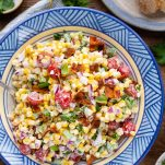 Overhead image of corn tomato salad in a blue bowl with bacon on top