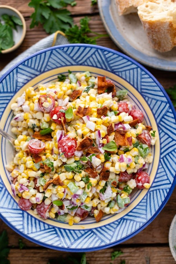 Overhead shot of fresh corn salad in a blue bowl with a side of bread