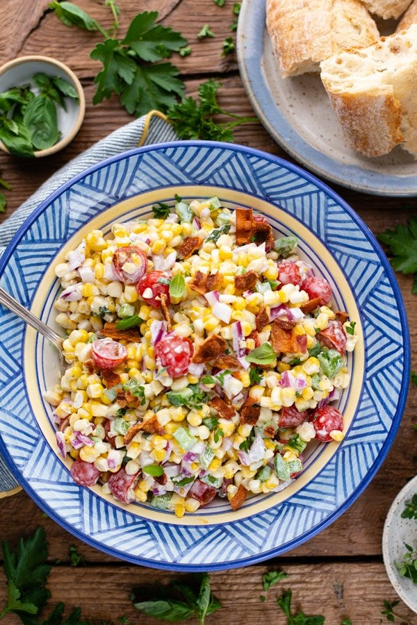 Bowl of creamy corn salad on a wooden table with herbs on the side