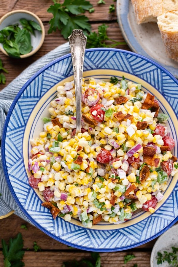 Close overhead shot of a bowl of summer corn salad with mayo