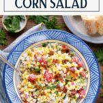 Bowl of cold corn salad on a wooden table with text title box at top