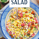 Overhead shot of a spoon in a bowl of creamy corn salad with text title overhead