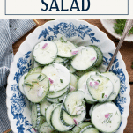 Overhead image of a bowl of cucumber dill salad on a table with text title box at top
