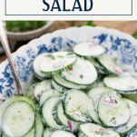 Close up side shot of a bowl of creamy cucumber salad with text title box at top