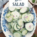 Overhead shot of a bowl of creamy cucumber salad with text title overlay