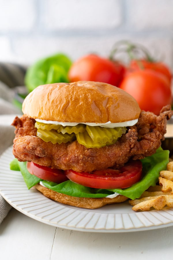 Close up shot of the best fried chicken sandwich recipe served on a plate with Chik Fil A sauce.