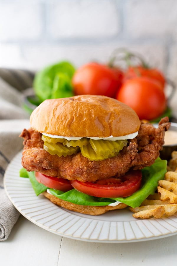 Front shot of a Chik-Fil-A fried chicken sandwich recipe served on a white plate with a side of fries