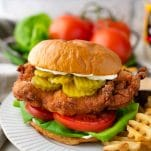 Side shot of a homemade fried chicken sandwich on a plate with fries