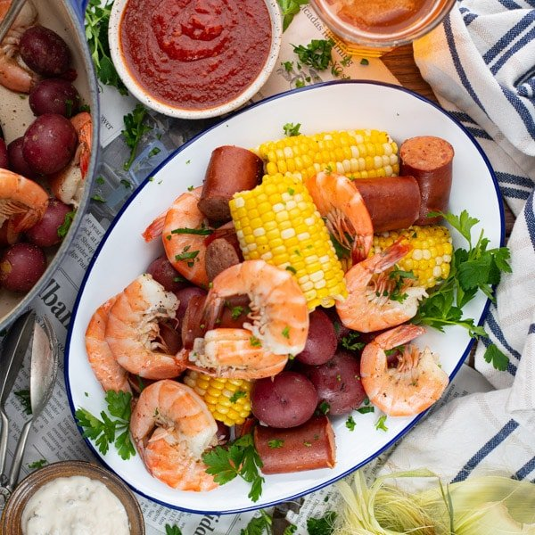 Square overhead image of a platter of Frogmore stew on a picnic table with beer and dip