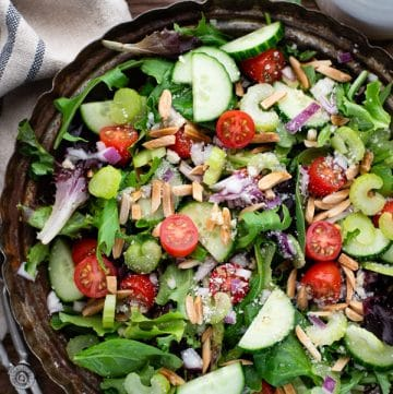 Close overhead shot of a bowl of the best green salad recipe served with homemade vinaigrette dressing