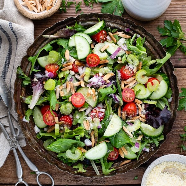 Overhead square image of a bowl of mixed green salad on a wooden table with a side of parmesan