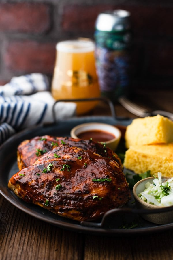 Side shot of grilled bbq chicken on a table with a brick wall in the background
