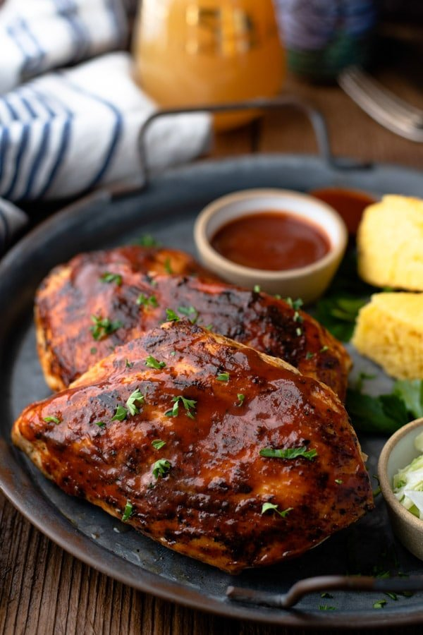 Close up side shot of grilled bbq chicken breast on a platter with sides and bbq sauce