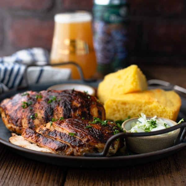 Square image of grilled bbq chicken on a plate with sides and a drink in the background