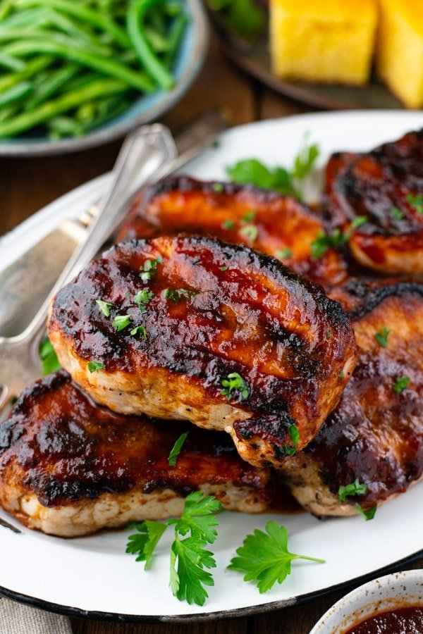 Close up shot of tender grilled bbq pork chops on a white platter and served with a side of cornbread