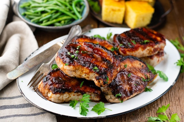 Horizontal shot of a tray of grilled bbq pork chops with a side of cornbread and green beans