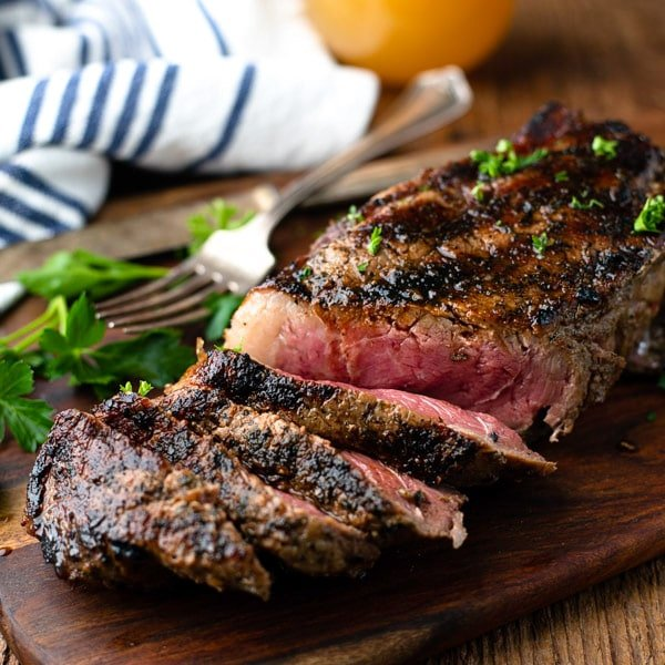 Close up square shot of a grilled New York Strip steak recipe on a cutting board with a cold beer in the background