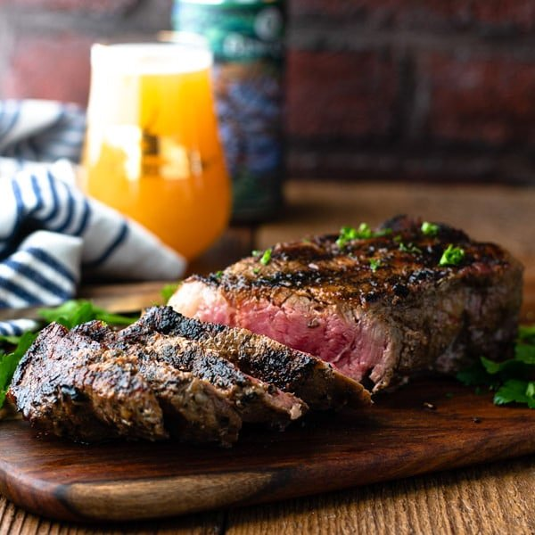 Square side shot of the best grilled strip steak recipe on a cutting board