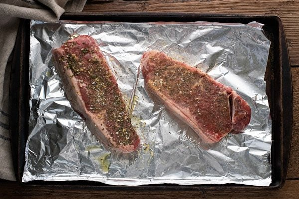 Overhead shot showing how to season New York Strip steak