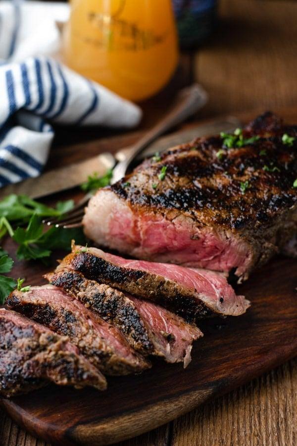 A sliced grilled New York Strip steak on a cutting board