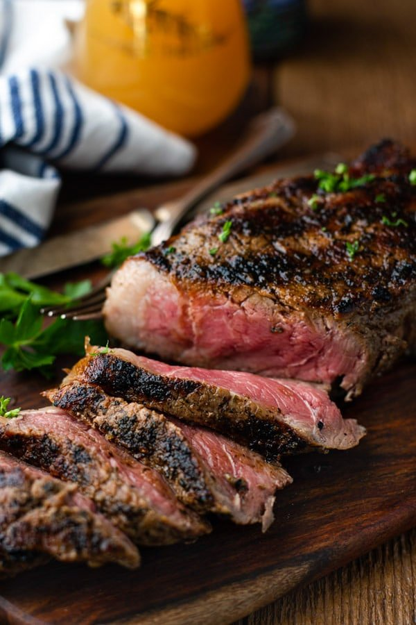 Close up front shot of grilled new york strip steak on a cutting board