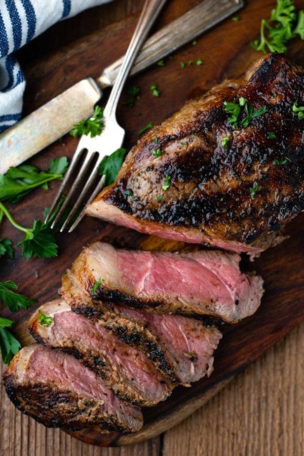 Overhead shot of grilled New York Strip Steak recipe on a cutting board
