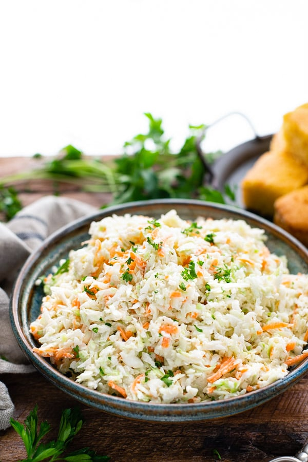 Side shot of traditional coleslaw recipe with cornbread in the background