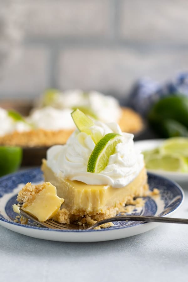 Front shot of an easy key lime pie recipe served on a plate and topped with whipped cream.
