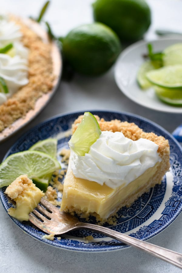 Slice of a homemade easy key lime pie recipe served on a blue and white plate with a bite on a fork