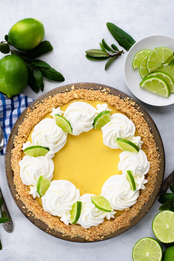 Overhead image of a traditional key lime pie recipe on a white surface
