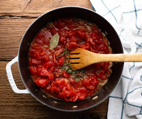 Diced tomatoes in a pot with herbs