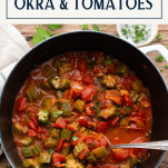 Overhead shot of white dutch oven with okra and tomatoes and a text title box at top
