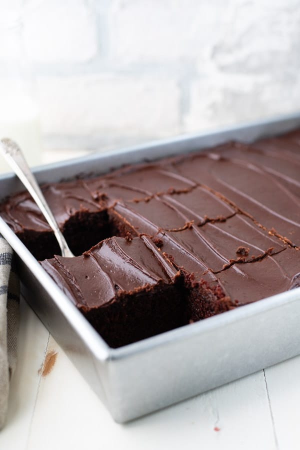 Side shot of a cake server lifting a slice of one bowl buttermilk chocolate cake from a pan