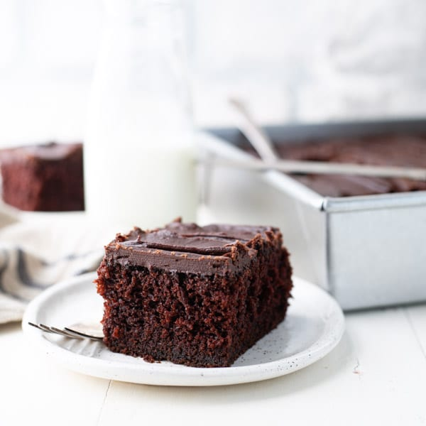 Square image of moist chocolate cake on a white surface