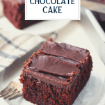 Slice of the best chocolate cake recipe on a white table with text title overlay