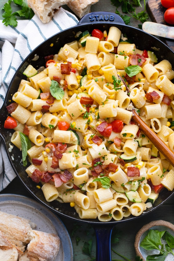Overhead shot of a cast iron skillet full of pasta with corn zucchini and tomatoes.