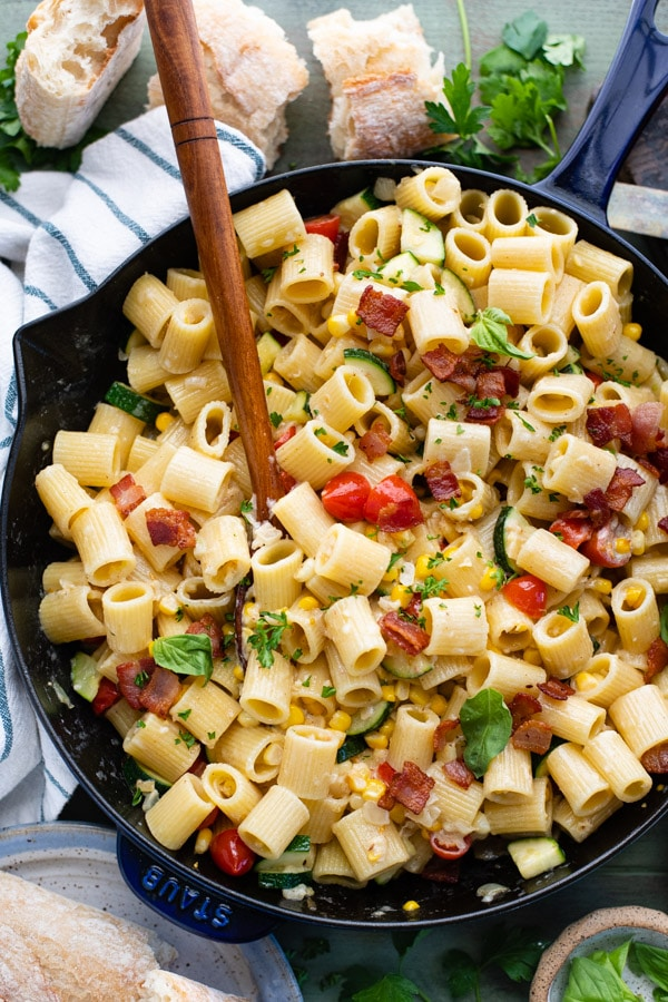 Close overhead image of a wooden spoon in a pan of pasta with corn and bacon