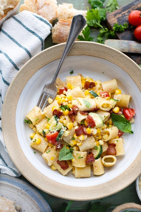 Close overhead image of pasta with corn and tomatoes