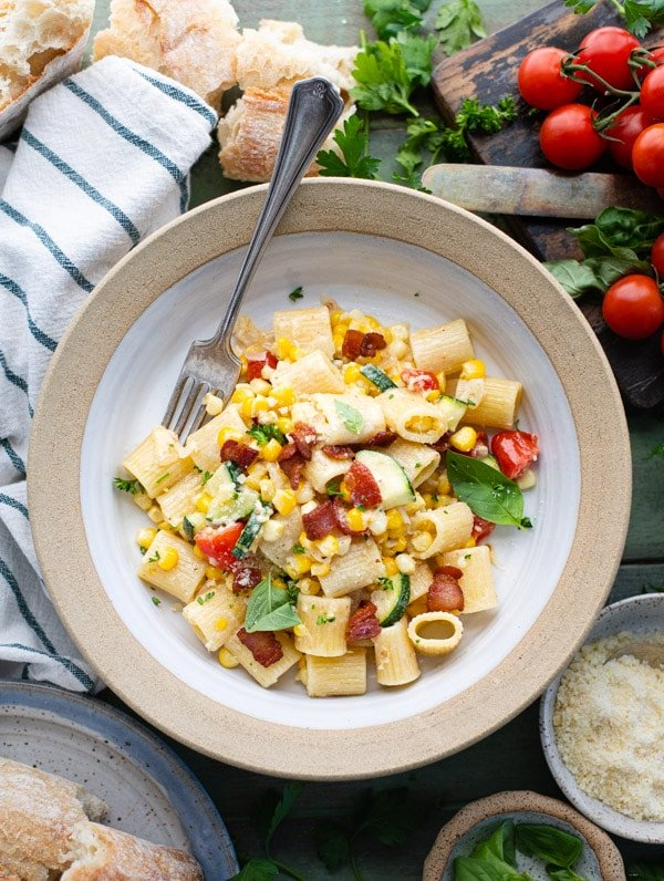 Overhead image of a bowl of pasta with sweet corn tomato and basil on a green table