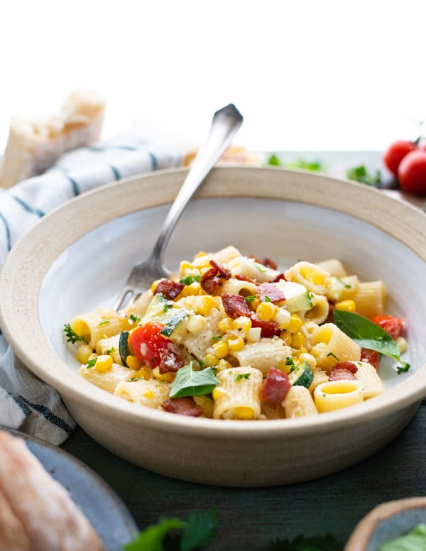 Side shot of a bowl of creamy corn pasta with basil