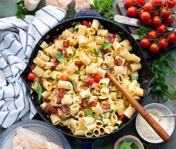Horizontal overhead shot of a cast iron skillet full of pasta with corn zucchini and tomatoes
