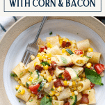 Overhead shot of a bowl of creamy corn pasta with basil and text title box at top