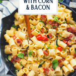 Skillet full of pasta with corn and tomatoes and text title overlay