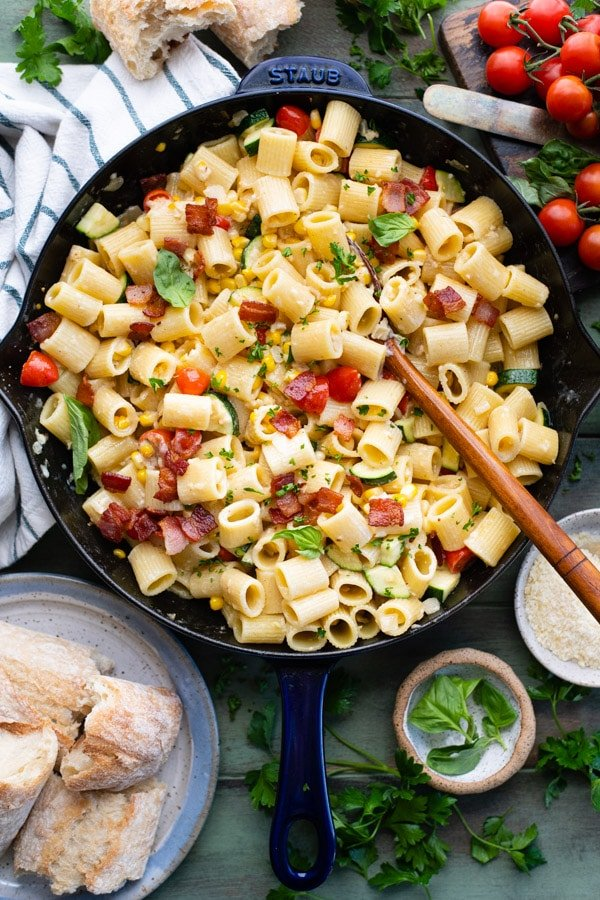 Overhead shot of a skillet full of creamy pasta with corn on a wooden table