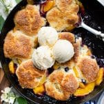 Close overhead shot of peach blueberry cobbler in a cast iron skillet