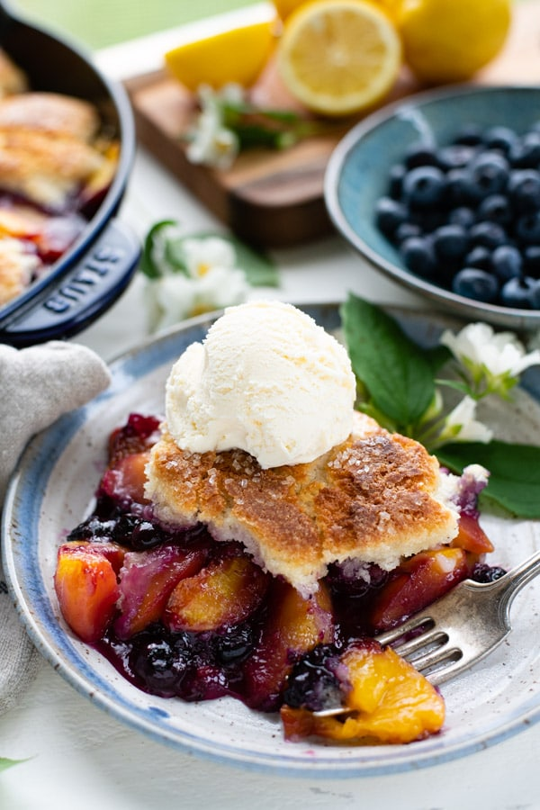 Close up side shot of southern peach blueberry cobbler on a plate with ice cream