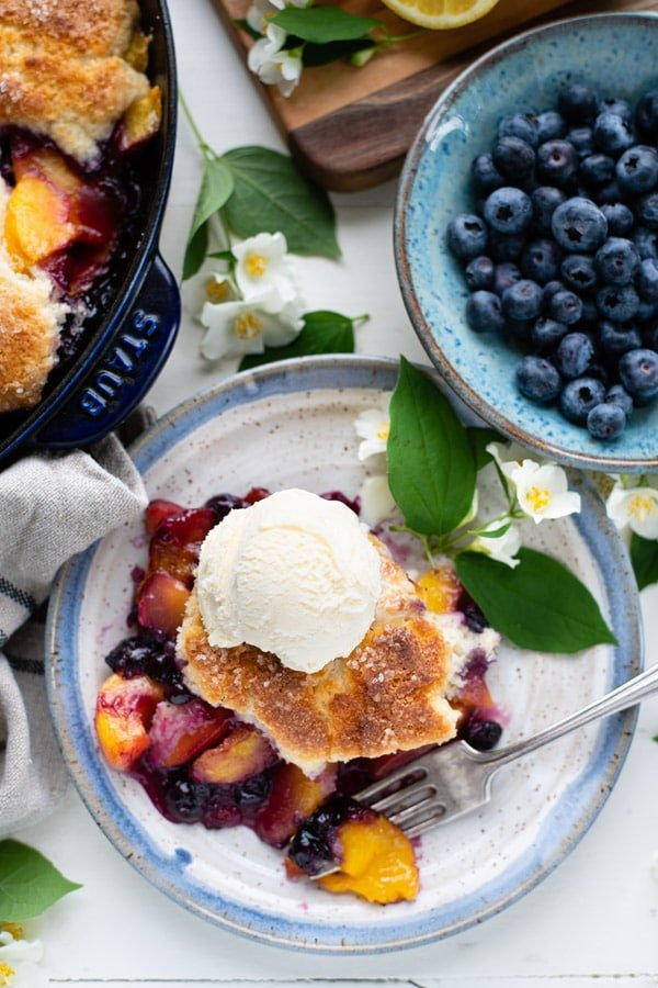 Overhead image of old fashioned peach and blueberry cobbler on a plate on a white table