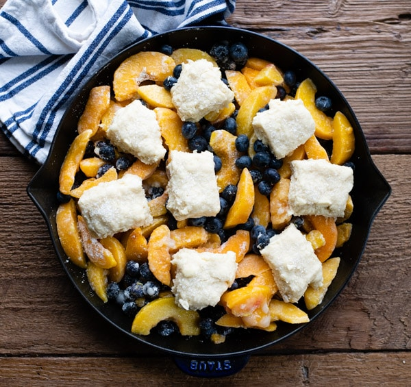 Process shot showing how to make southern peach blueberry cobbler in a cast iron skillet