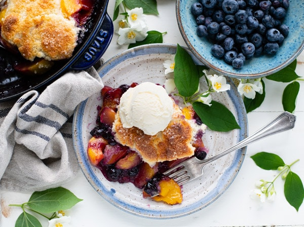 Horizontal overhead shot of easy blueberry peach cobbler on a plate with vanilla ice cream